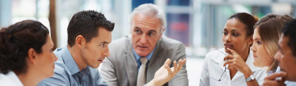 One man is speaking while others listen carefully in a business meeting